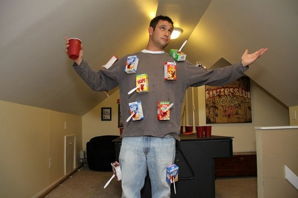 A man dressed in casual clothes for Halloween with cereal boxes taped on the front of his shirt.