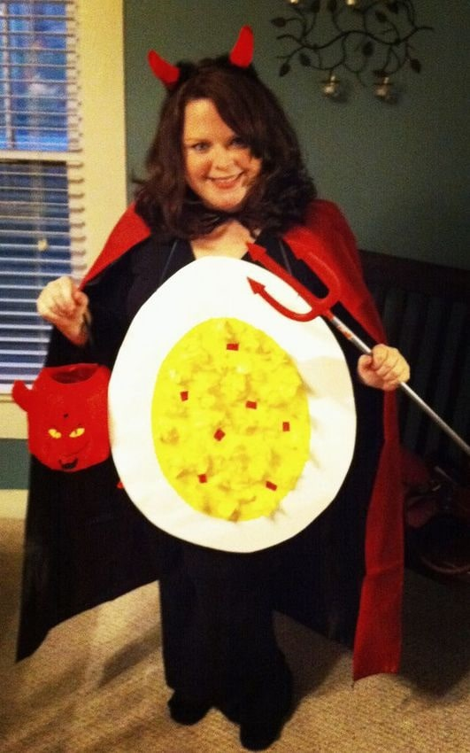 A woman dressed in a Halloween costume as the devil with a deviled egg model taped on her front.