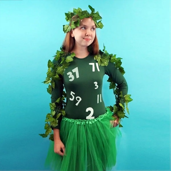 A woman dressed as an Amazon jungle goddess with prime numbers taped on the front part of her green top.