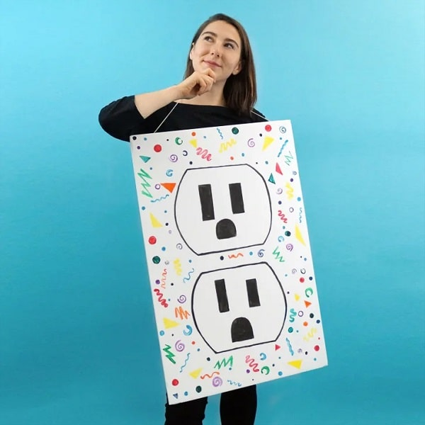 A woman dressed as a creative outlet for her Halloween costume made of a black ensemble with a drawing of an electric outlet with a colorful background hanging on her neck.