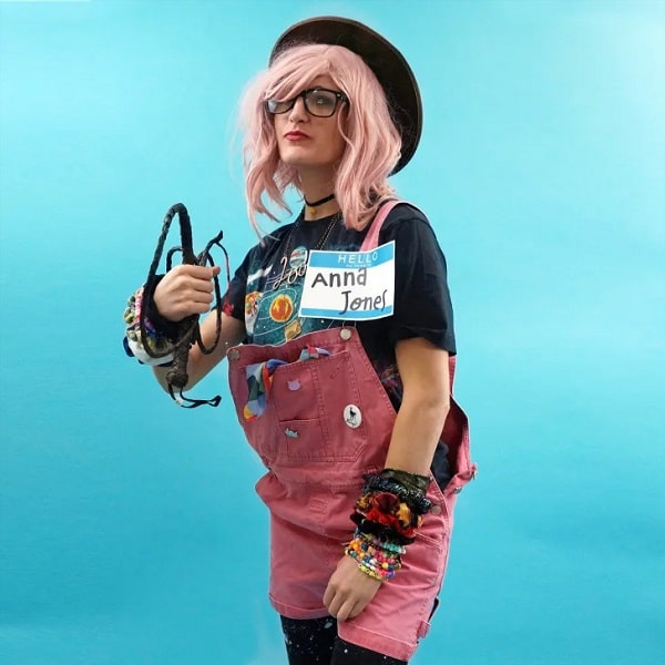 A woman dressed as Indie Anna Jones for her Halloween costume consisting of pair of pink overalls with matching nametag and whip.