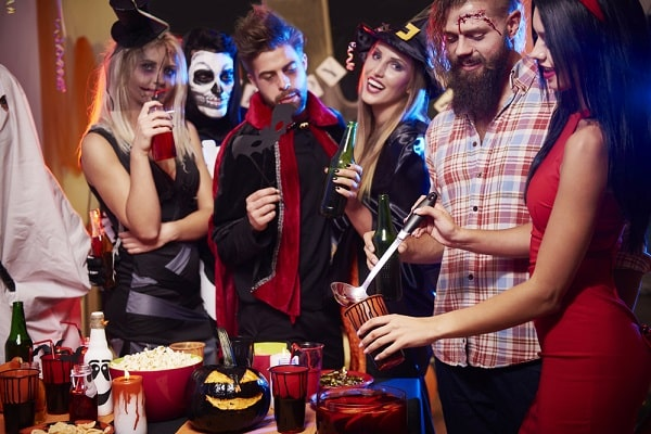 A group of friends at a party dressed in their Halloween costumes.