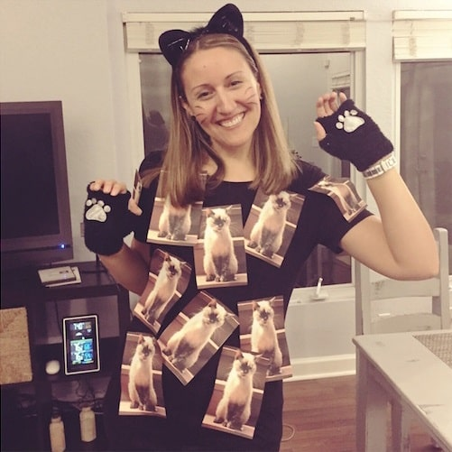 A woman wearing a Halloween costume made of a catsuit with cat photos taped on her black shirt.