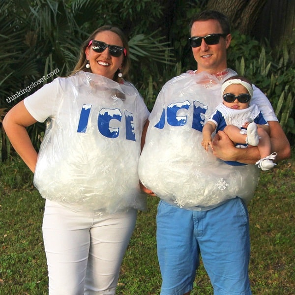 A couple wearing Halloween costumes made of ice bags and sunglasses, holding a baby with a matching outfit.