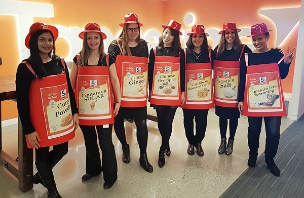 A group of women dressed as spice girls for their Halloween costume made of a black ensemble and pictures of different spices hanging on their necks.