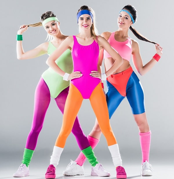 Three women in their colorful '80s aerobics apparel, with Spandex leotards and leg warmers.