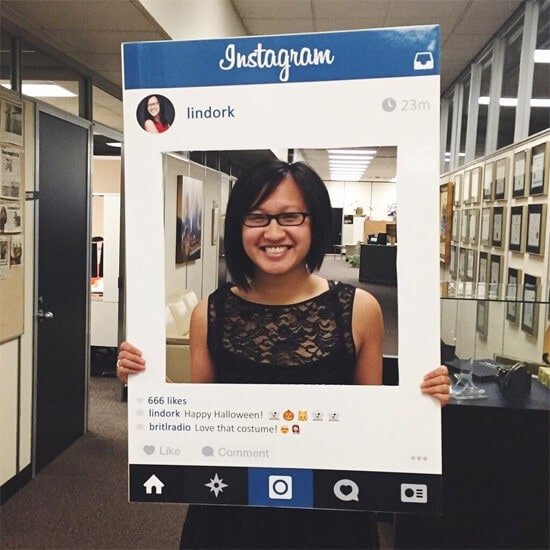 A short-haired girl with glasses in a DIY Instagram post costume.