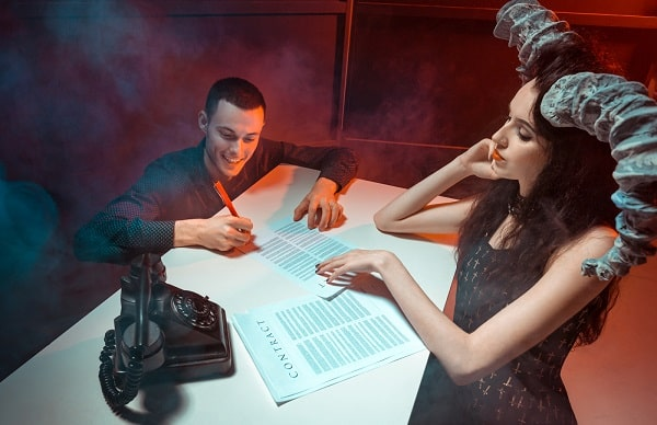 A woman wearing a black vintage gothic dress and a gray headdress with gray devil horns, making a man sign a contract.