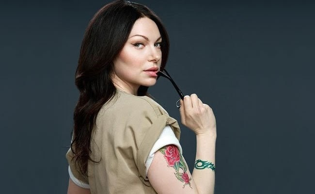 Alex Vause from the TV series Orange Is the New Black, wearing her prison suit, tattoos, and holding her specs in her hand.