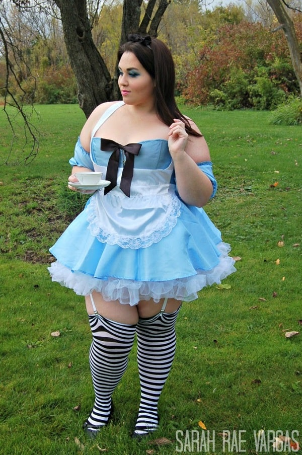 A woman in an Alice in Wonderland Halloween costume, with the iconic white and blue dress with matching black and white striped knee-high socks.