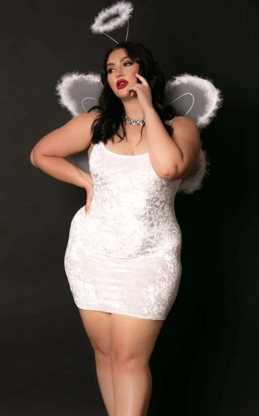 A woman in an angel Halloween costume, with a short white dress and angel wings plus halo.