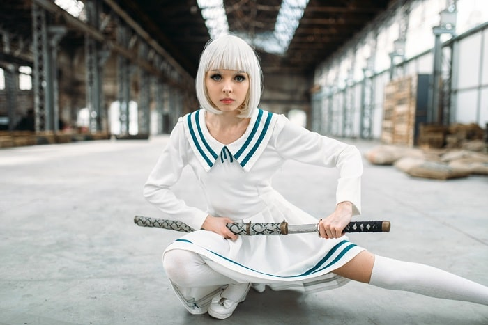 A woman dressed as an anime character, wearing her blue and white sailor-style dress, platinum-blonde hair, and oriental weapon.