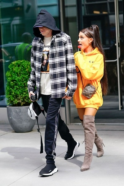 A photo of Ariana Grande in an oversized yellow hoodie and thigh-high boots, walking with Pete Davidson.
