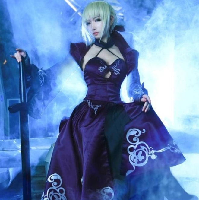 A woman dressed as Artoria Pendragon from Fate/Stay Night, in a blue gown and blonde hair.