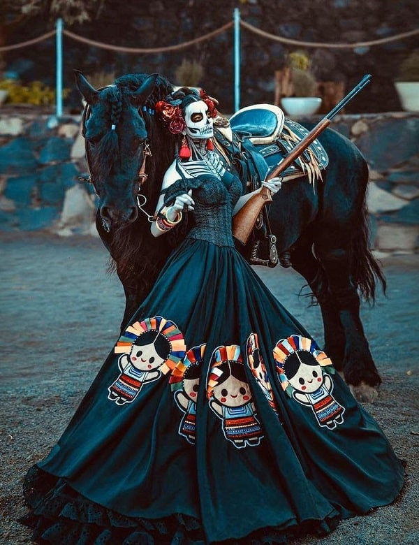 A woman in a Day of the Dead costume, wearing a black corset ball gown with colorful patches.
