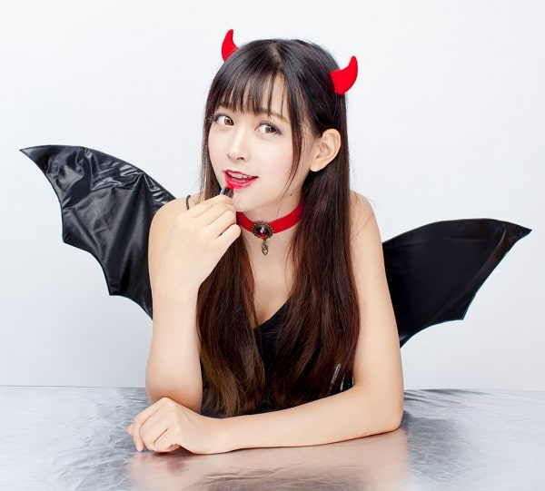 A woman in a bat-devil duo costume, wearing black lingerie, a red choker, red horns, and red lipstick.