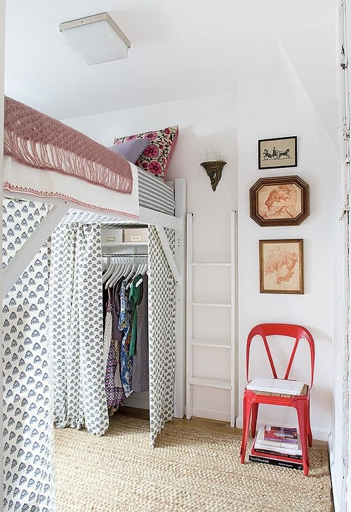 A dorm room design with a free-standing closet under the bed, hidden by printed curtains.