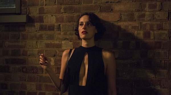 Phoebe Waller-Bridge from a scene in the TV show Fleabag, with her leaning against a brick wall, holding a cigarette in her hand.