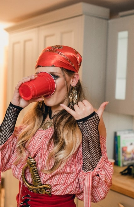 A woman in a boho pirate college babe costume, drinking from a red cup.