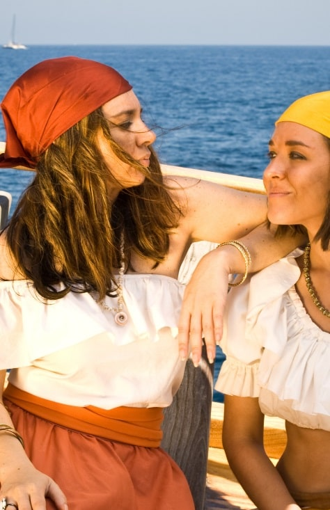 Two women on a boat, wearing breezy light-colored beach outfits.