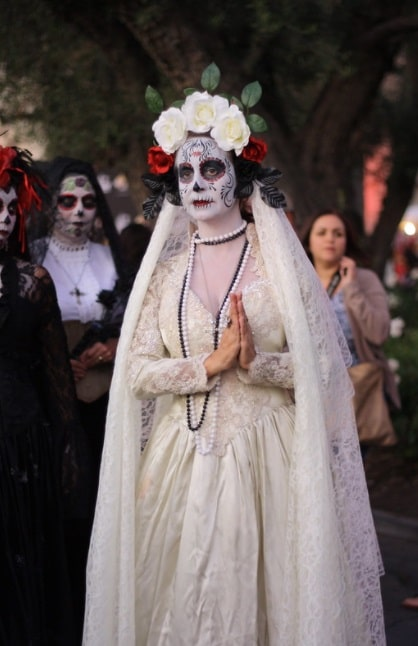 A woman wearing a bride costume with matching face paint for Day of the Dead