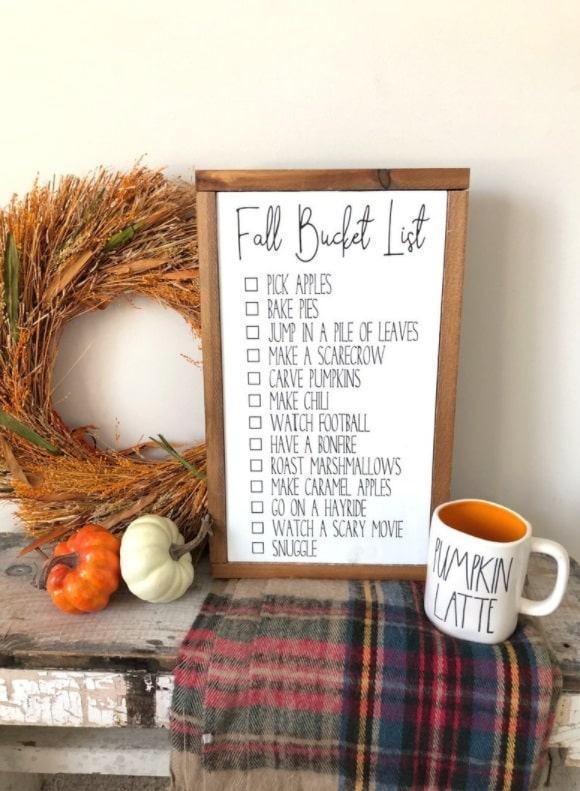 A fall bucket list-themed dorm room with a framed bucket list, autumn-inspired coffee mug, and harvest wreath on a wooden desk.