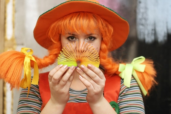 A woman dressed as Pippi Longstocking, with a striped shirt, orange overalls, and the iconic braided hair.