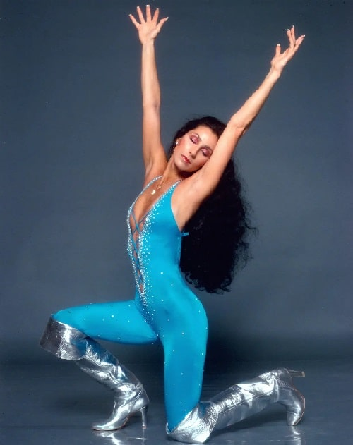 A photo of a young Cher in a blue outfit and silver boots.