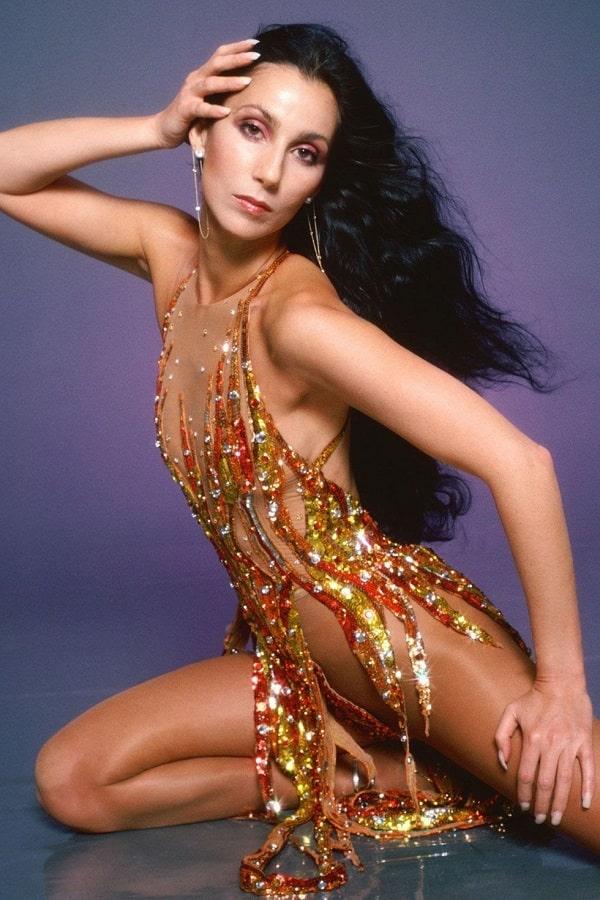 Cher in her '70s look with long black hair, dangling earrings, and sparkly Bob Mackie dress.