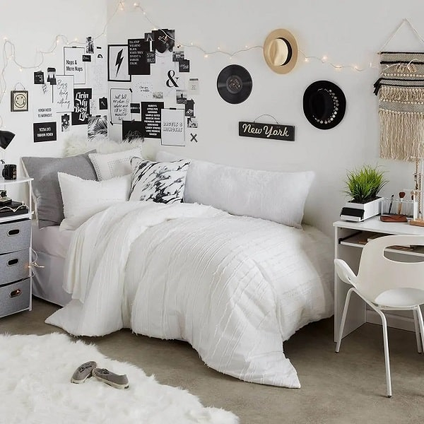 A modern black and white dorm room with a white comforter, marble-print throw pillow, and a woven macramé wall tapestry.