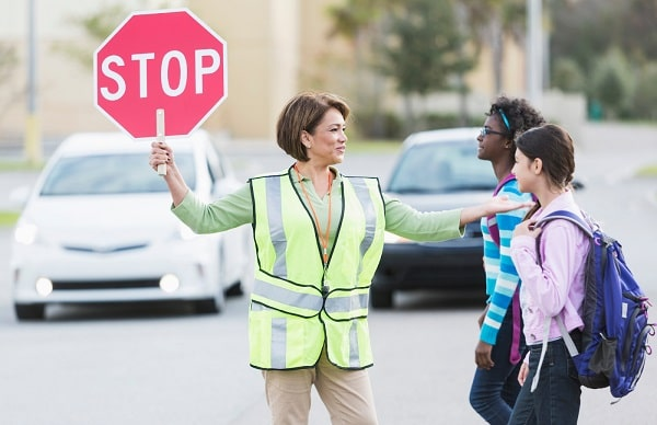 A crossing guard holding a stop sign and wearing a yellow vest with a whistle around her neck.