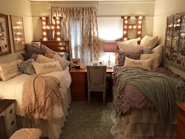A glitzy dorm room with throw pillows of various designs that complement the glammed up aesthetic.
