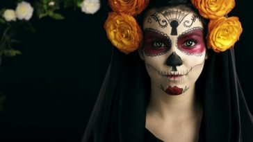 A woman in a Day of the Dead attire, wearing a black gown, intricate face paint, and a yellow flower crown.