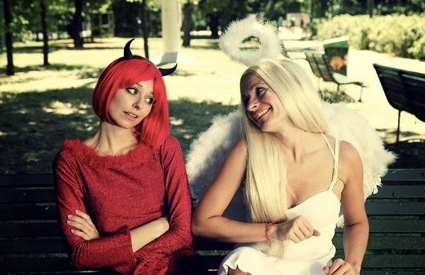 Two women in a devil-angel Halloween duo costume, sitting on a park bench.