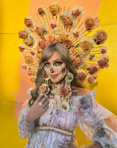 A woman in a Day of the Dead costume, wearing a spiked headdress adorned with dried flowers and a floral-print dress.