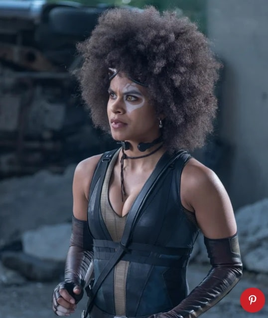 Domino from the movie Deadpool, wearing a tight leather top with matching fingerless gloves and white face paint.