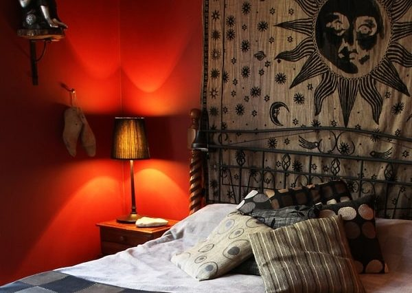 A sun and stars tapestry hung above the bed of a rustic-themed college dorm room.