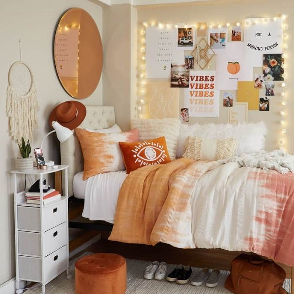 A relaxed glam dorm room with a velvet ottoman and a circle wall mirror hung above the bed with pink and gold sheets.