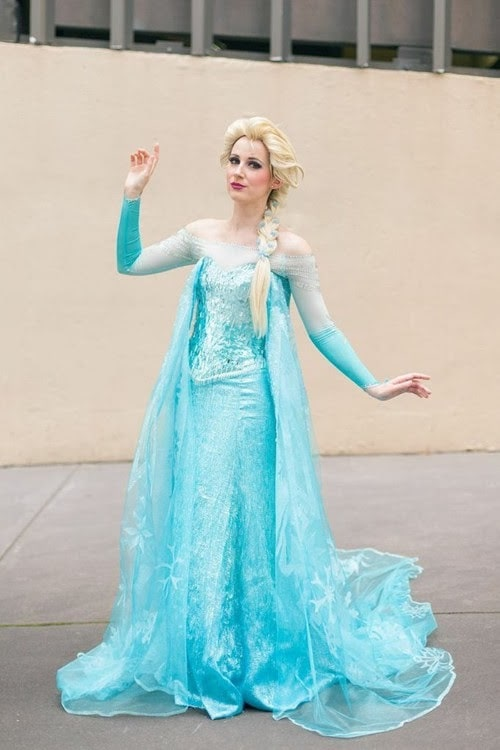 A woman in an Elsa from Frozen Halloween costume, wearing her iconic blue gown and braided blonde hair.
