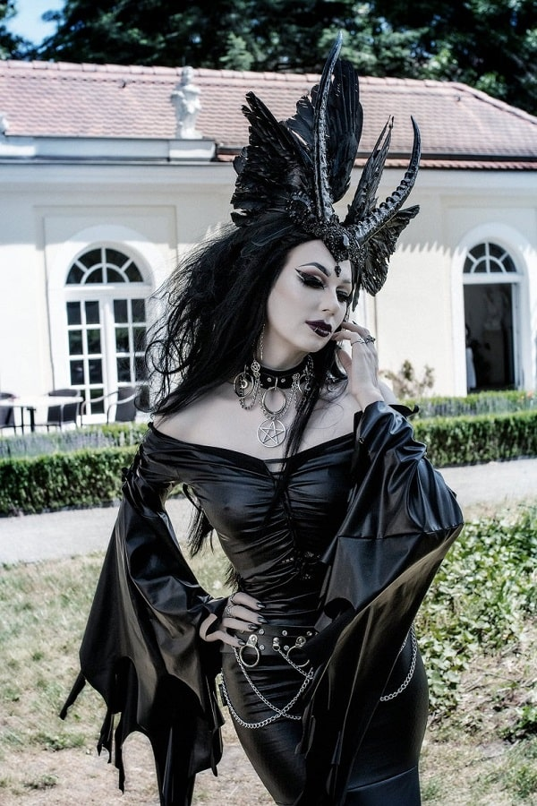 A woman in a gothic beauty queen devil Halloween costume, wearing a black dress, black horns with raven wings, and a leather harness with chains.