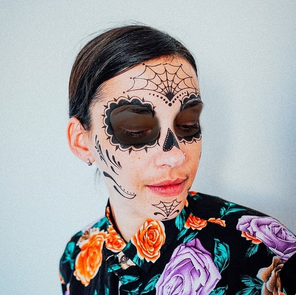 A woman wearing a floral-print top and temporary Day of the Dead face tattoos.