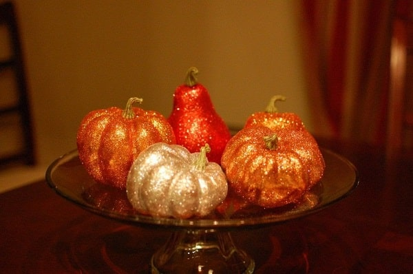 A collection of glittery pumpkins laid out on a cake stand atop a glass table.