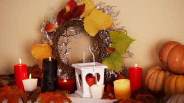 A festive fall-themed corner adorned with a wreath and dried leaves, candles of various fall colors, and some pumpkins on the side.