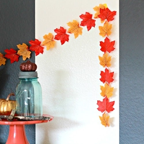 Fall-inspired dorm room decor using a garland made of orange and yellow faux fall leaves hung against a white backdrop.