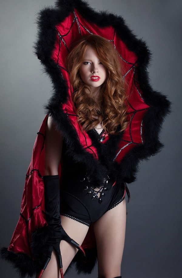 A woman wearing a fashion-forward devil costume, with a black corset, couture collar, and black gloves with claws.
