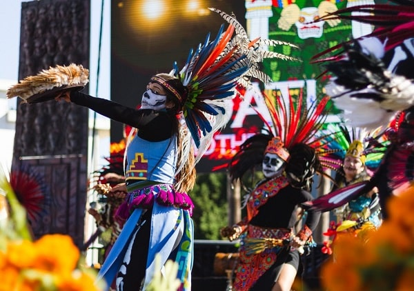 Day of the Dead dancers portraying the eagle and the jaguar with headdresses made of colorful feathers, face paint, and vibrant costumes.