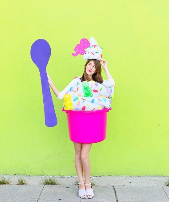 A woman in a froyo costume with a pink muck tub and a giant purple spoon.