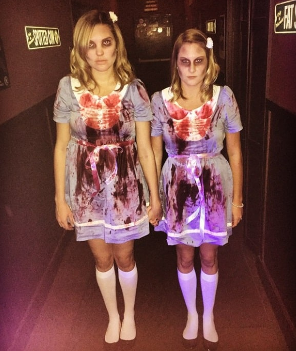 Two women dressed as the Grady twins, with bloody costumes inspired by the movie The Shining.