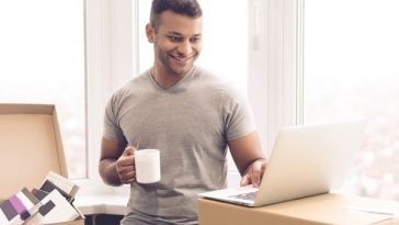 A guy with moving in boxes, drinking coffee and browsing on his laptop.