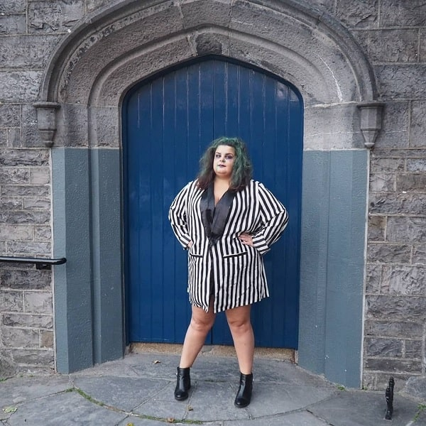 A woman wearing a Beetlejuice-inspired Halloween costume with the iconic green hair and black and white stripes on an oversized blazer.